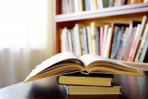 bigstock-An-Open-Book-With-Bookshelves--54102095